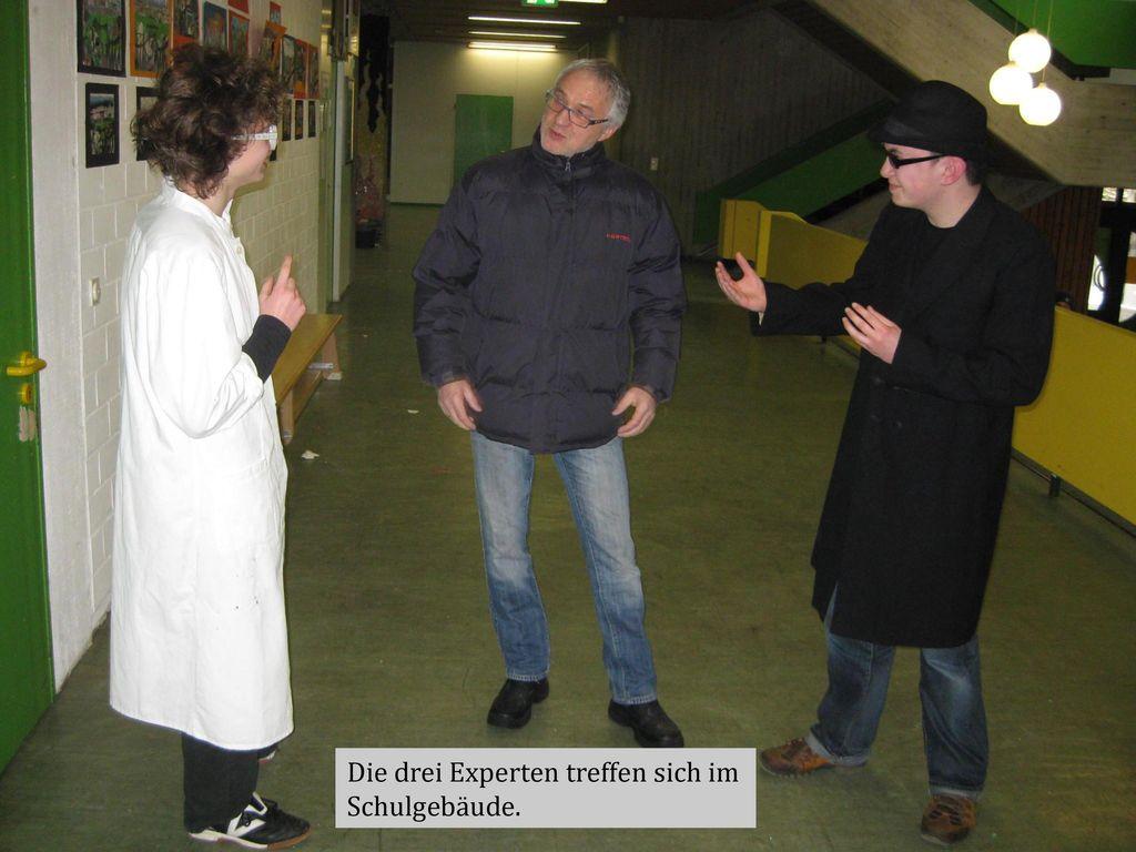Die drei Experten treffen sich im Schulgebäude.