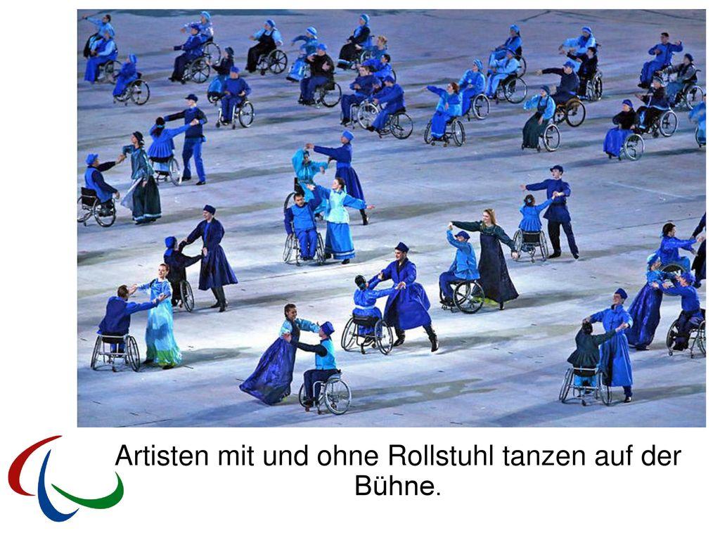 Artisten mit und ohne Rollstuhl tanzen auf der Bühne.