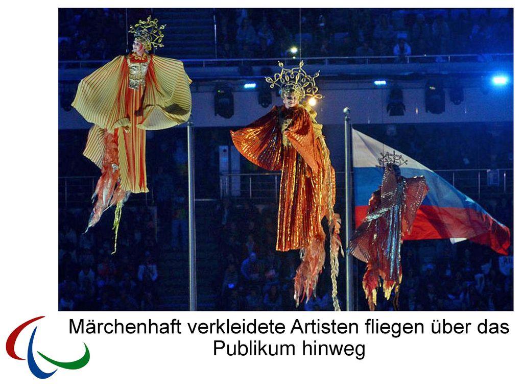 Märchenhaft verkleidete Artisten fliegen über das Publikum hinweg