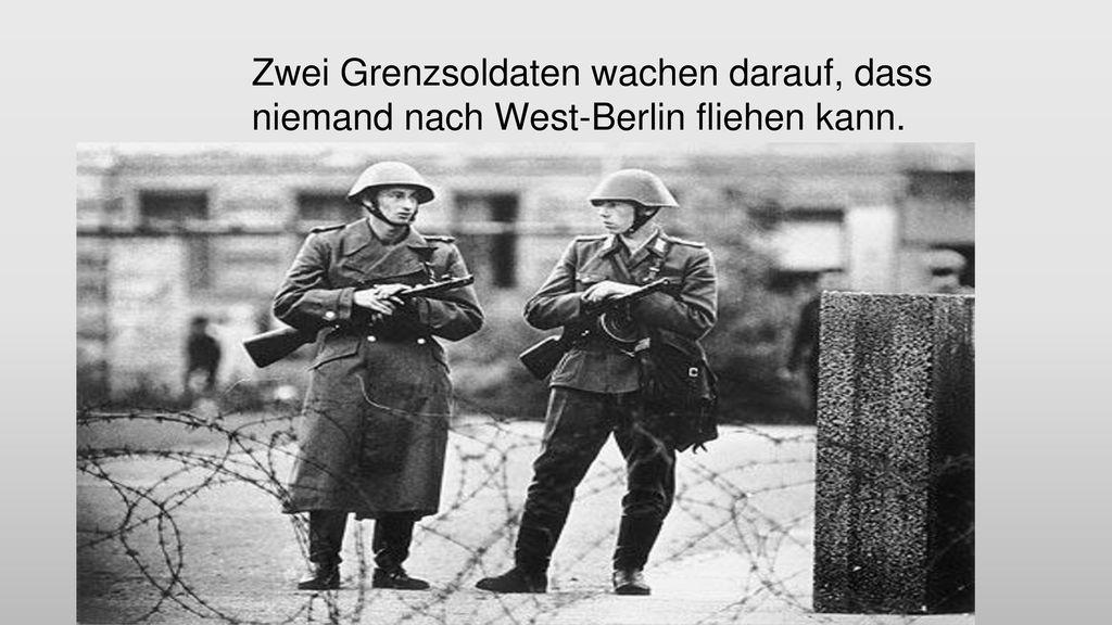 Zwei Grenzsoldaten wachen darauf, dass niemand nach West-Berlin fliehen kann.