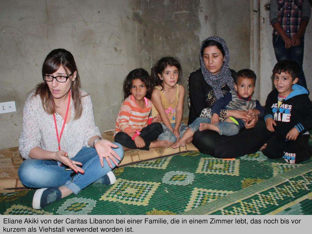 Eliane Akiki von der Caritas Libanon bei einer Familie, die in einem Zimmer lebt, das noch bis vor kurzem als Viehstall verwendet worden ist.