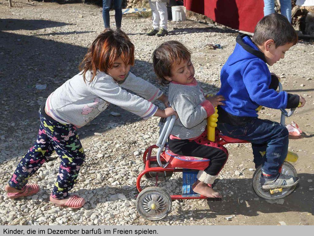 Kinder, die im Dezember barfuß im Freien spielen.