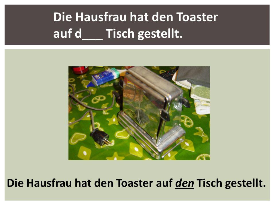 Die Hausfrau hat den Toaster auf d___ Tisch gestellt.