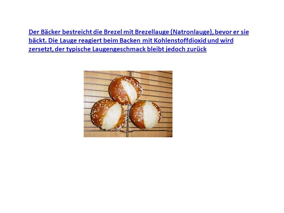 Der Bäcker bestreicht die Brezel mit Brezellauge (Natronlauge), bevor er sie bäckt.