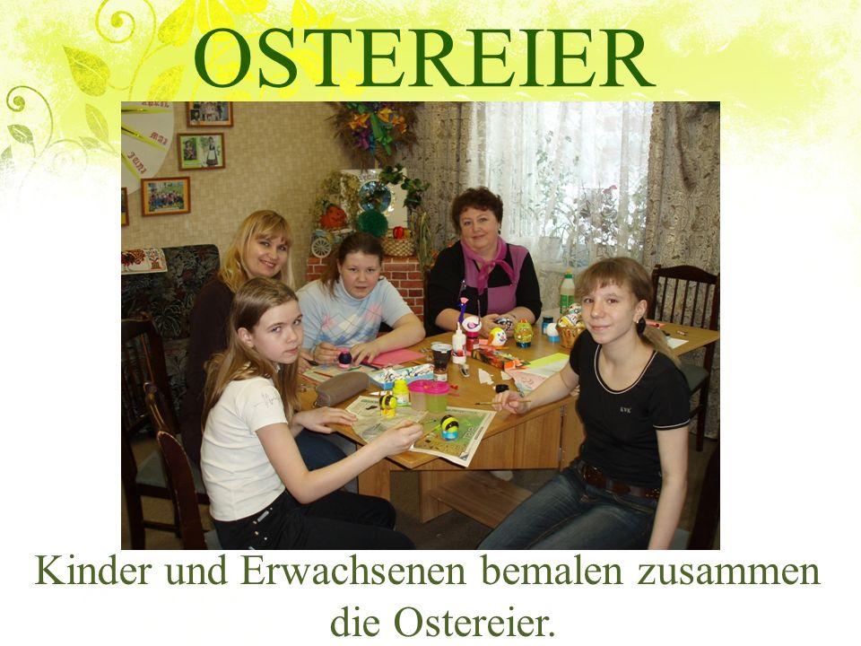 Kinder und Erwachsenen bemalen zusammen die Ostereier.
