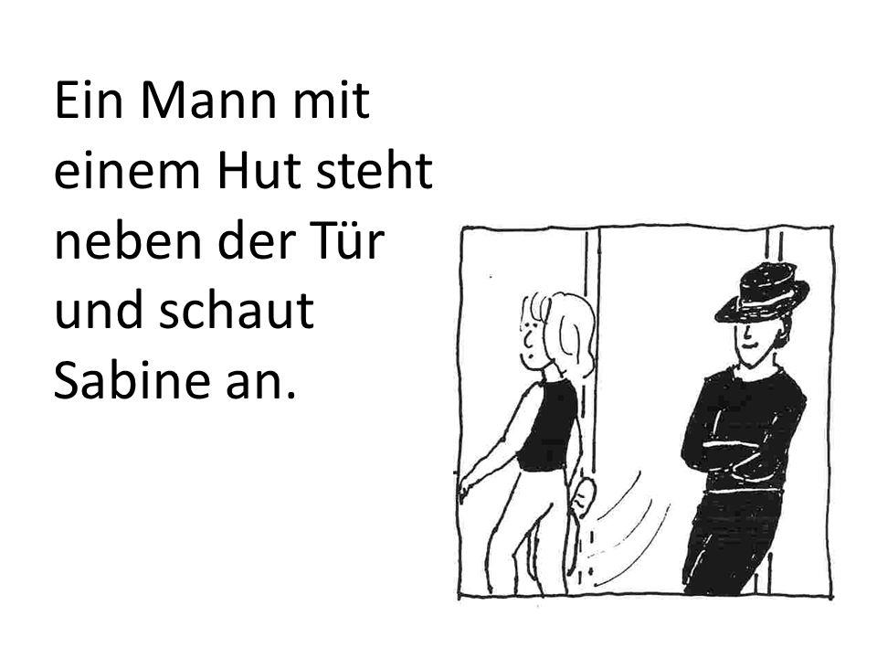 Ein Mann mit einem Hut steht neben der Tür und schaut Sabine an.