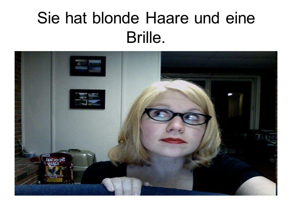 Sie hat blonde Haare und eine Brille.