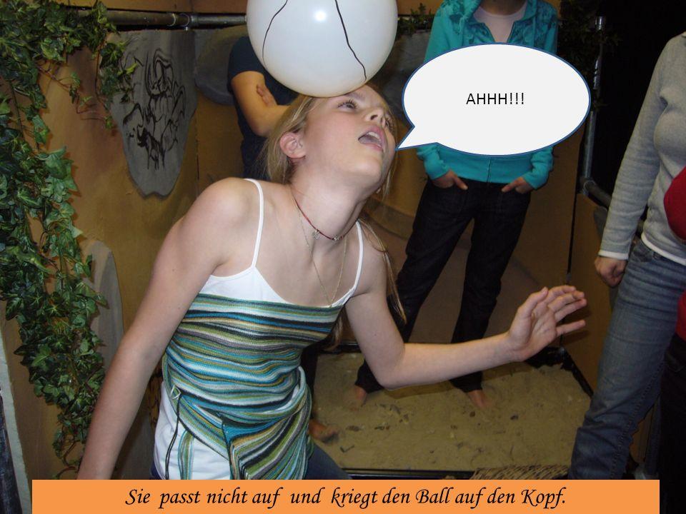 Sie passt nicht auf und kriegt den Ball auf den Kopf.