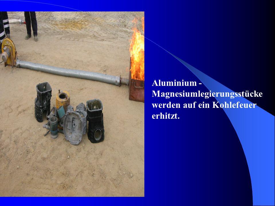 Aluminium - Magnesiumlegierungsstücke werden auf ein Kohlefeuer erhitzt.