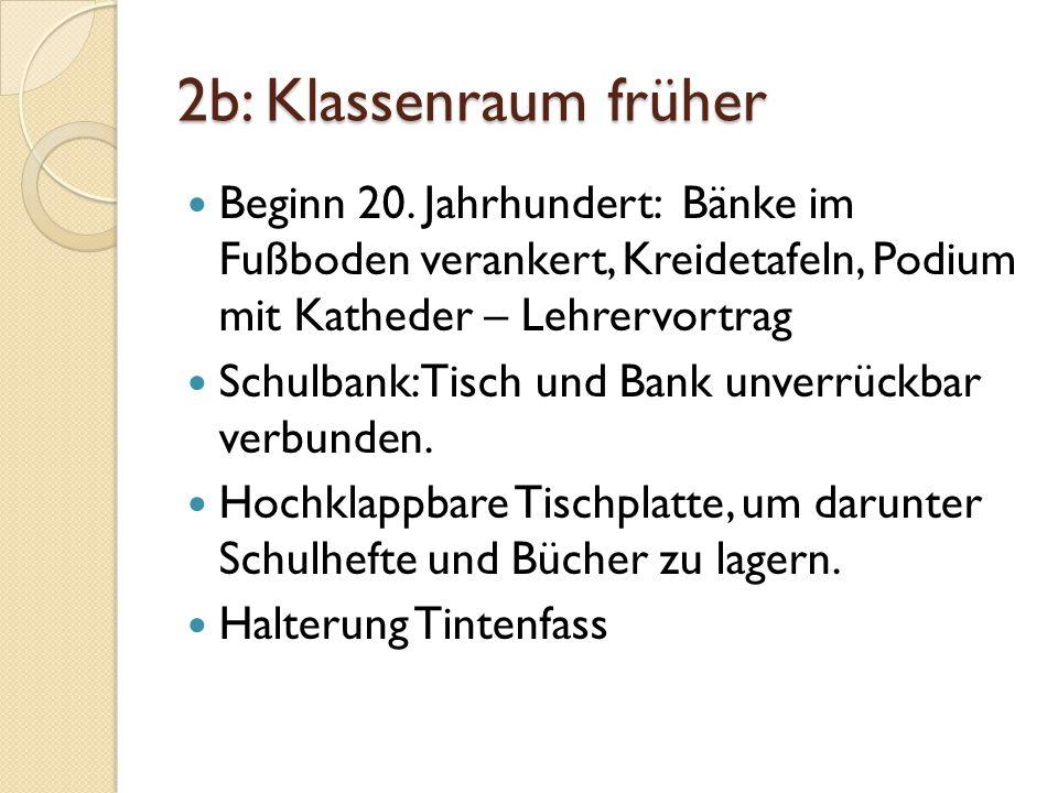 2b: Klassenraum früher Beginn 20. Jahrhundert: Bänke im Fußboden verankert, Kreidetafeln, Podium mit Katheder – Lehrervortrag.