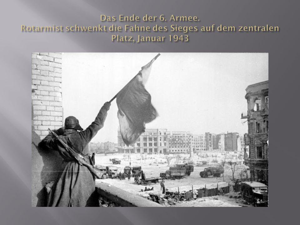 Das Ende der 6. Armee. Rotarmist schwenkt die Fahne des Sieges auf dem zentralen Platz, Januar 1943