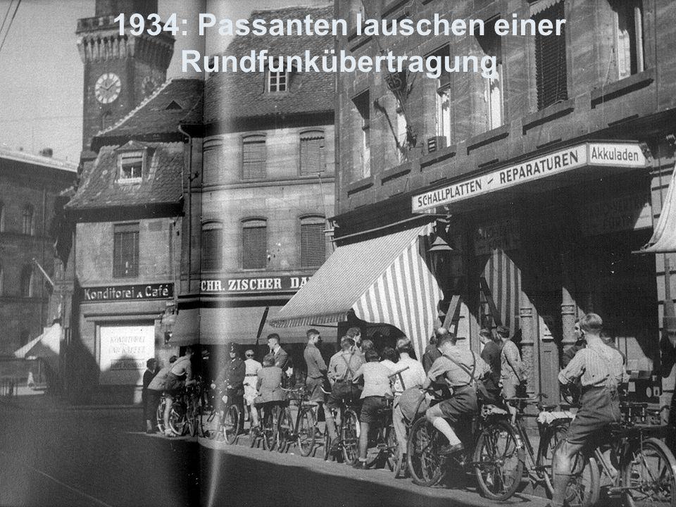1934: Passanten lauschen einer Rundfunkübertragung