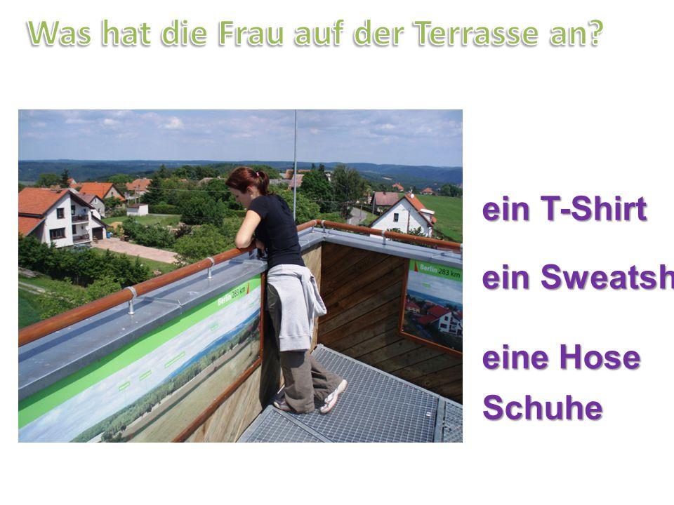 Was hat die Frau auf der Terrasse an