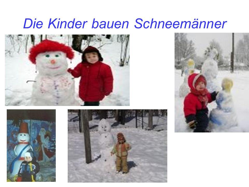 Die Kinder bauen Schneemänner