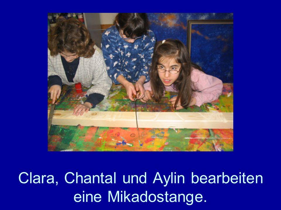 Clara, Chantal und Aylin bearbeiten eine Mikadostange.