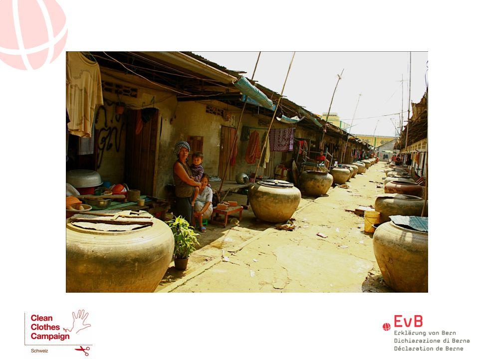 Kambodscha: Wohnviertel in unmittelbarer Nähe einer Fabrik – die Frauen arbeiten rund 60-80h/Woche, das ist der Wohnlevel, den sie sich leisten können (Kübel=stehendes Wasser, Infektionsgefahr); Toilette: ca.