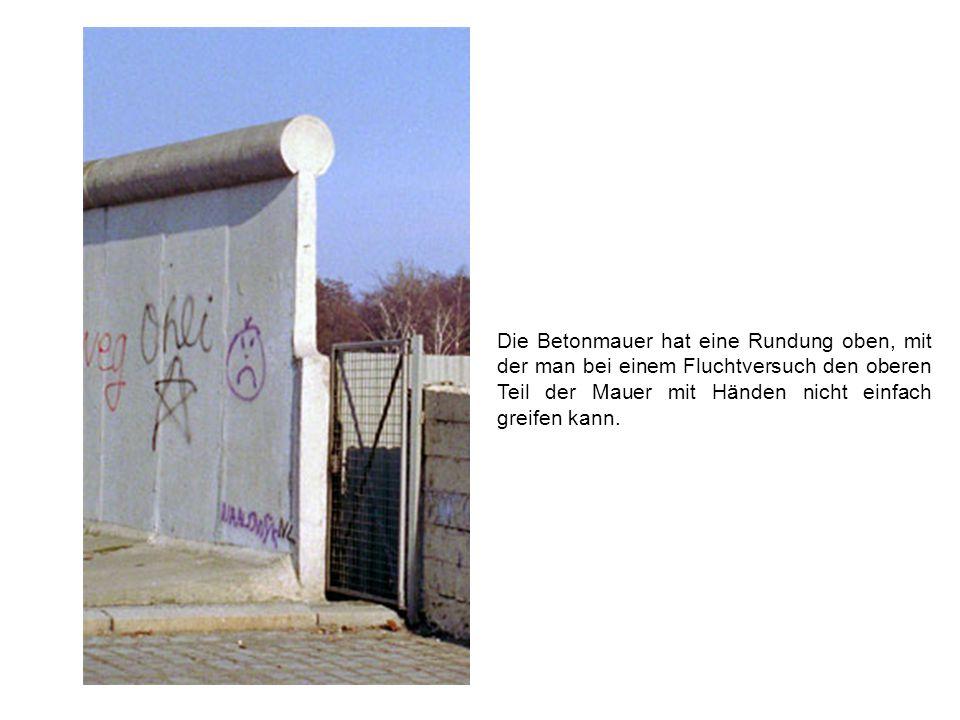 Die Betonmauer hat eine Rundung oben, mit der man bei einem Fluchtversuch den oberen Teil der Mauer mit Händen nicht einfach greifen kann.