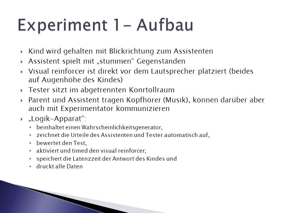 """Experiment 1- AufbauKind wird gehalten mit Blickrichtung zum Assistenten. Assistent spielt mit """"stummen Gegenständen."""