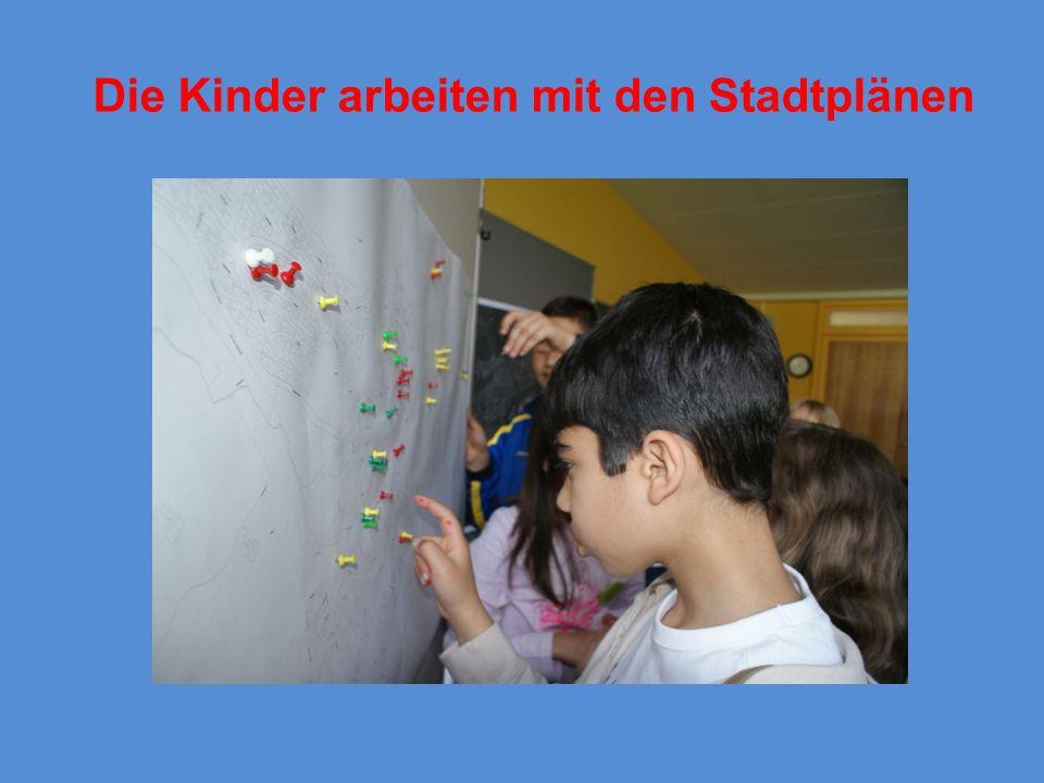 Die Kinder arbeiten mit den Stadtplänen