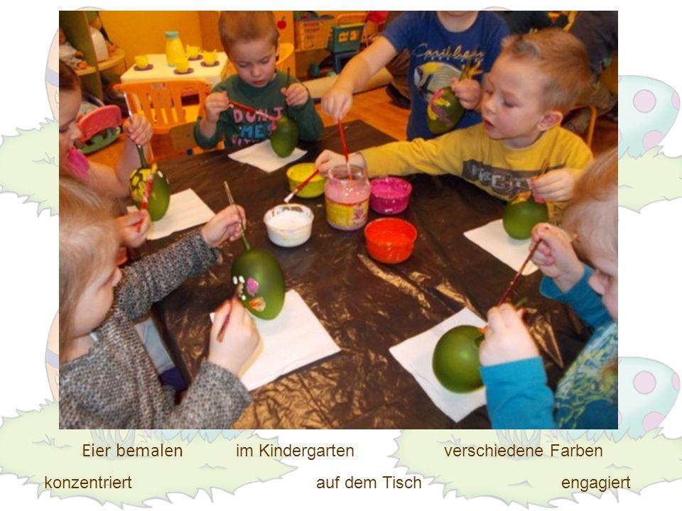 Eier bemalen im Kindergarten verschiedene Farben konzentriert