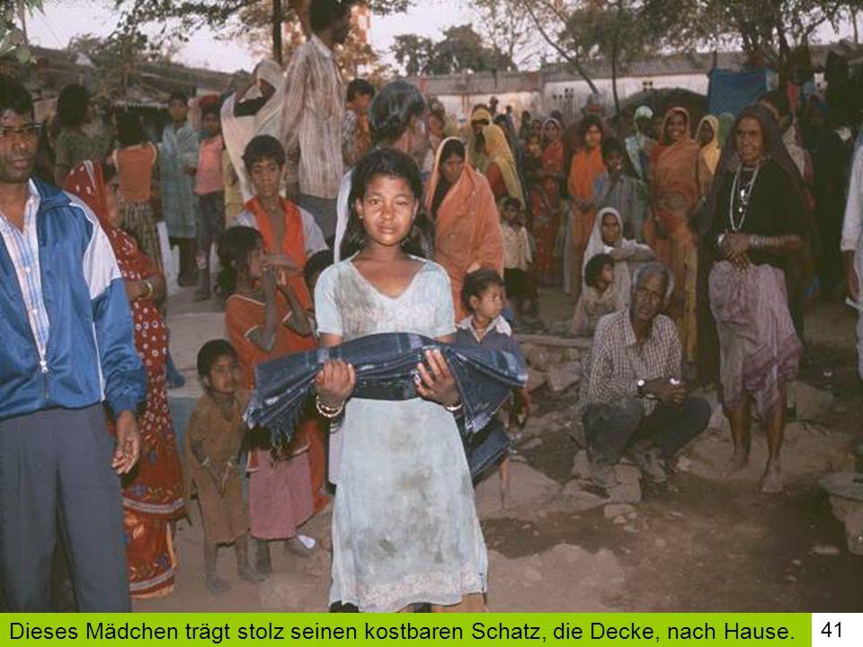 Dieses Mädchen trägt stolz seinen kostbaren Schatz, die Decke, nach Hause.