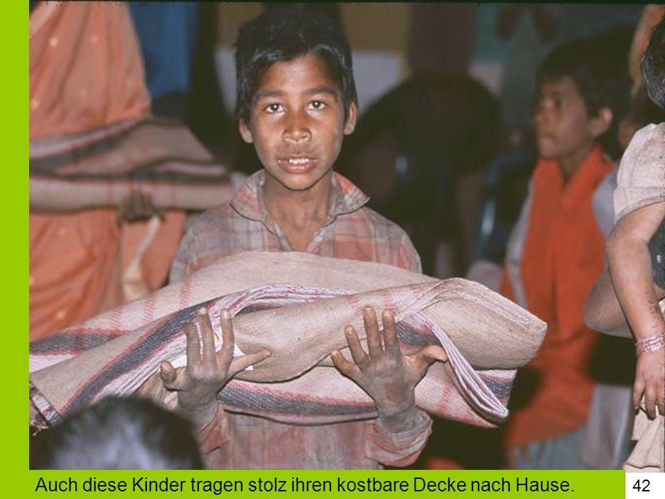 Auch diese Kinder tragen stolz ihren kostbare Decke nach Hause.