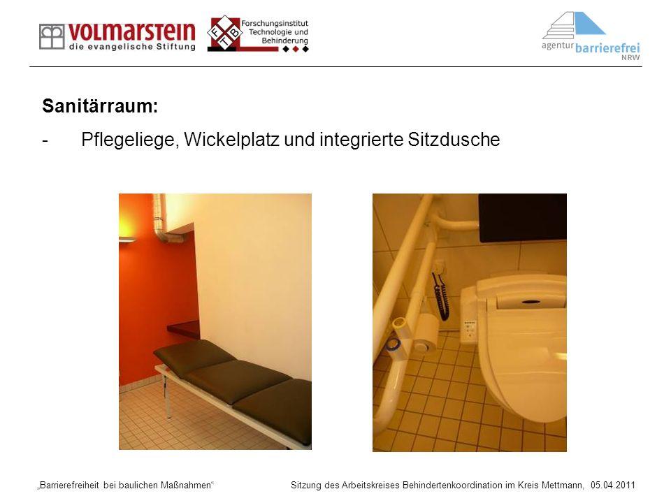 Sanitärraum: Pflegeliege, Wickelplatz und integrierte Sitzdusche