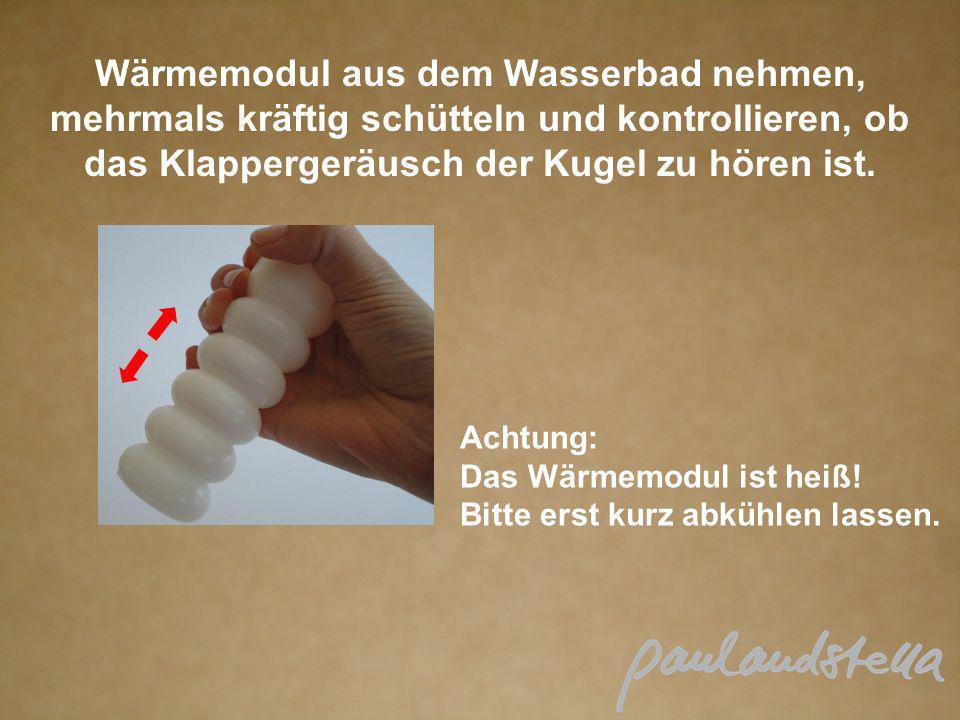 Wärmemodul aus dem Wasserbad nehmen, mehrmals kräftig schütteln und kontrollieren, ob das Klappergeräusch der Kugel zu hören ist.