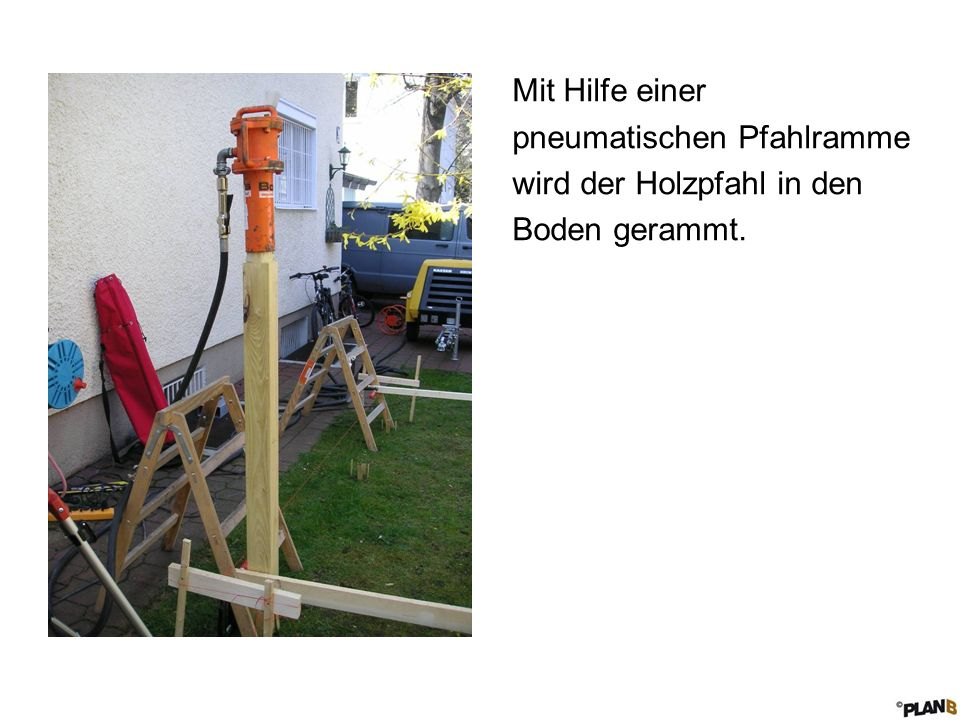 Mit Hilfe einer pneumatischen Pfahlramme wird der Holzpfahl in den Boden gerammt.