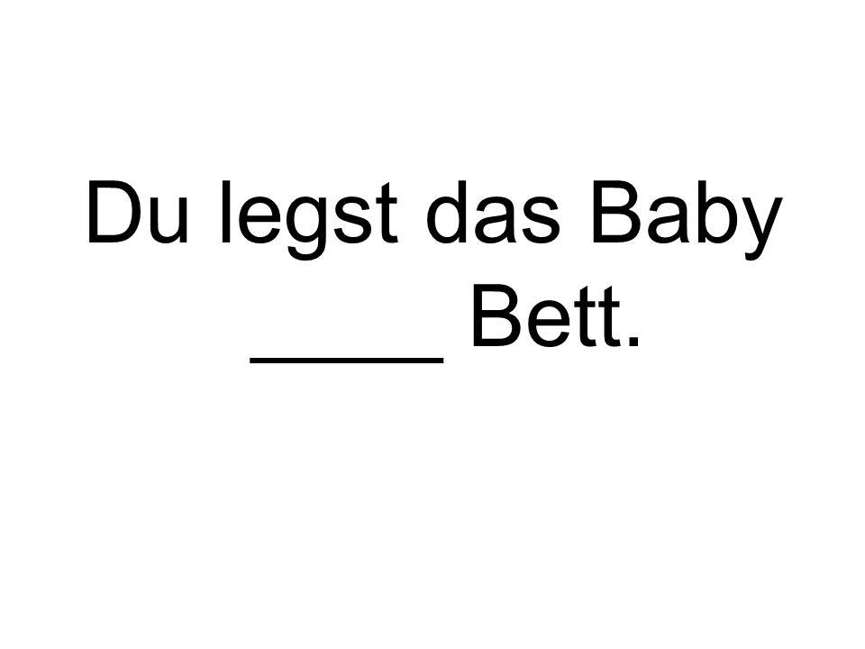 Du legst das Baby ____ Bett.