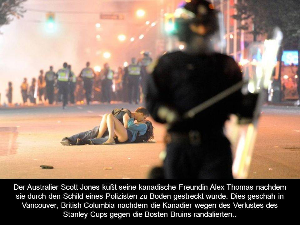 Der Australier Scott Jones küßt seine kanadische Freundin Alex Thomas nachdem sie durch den Schild eines Polizisten zu Boden gestreckt wurde.