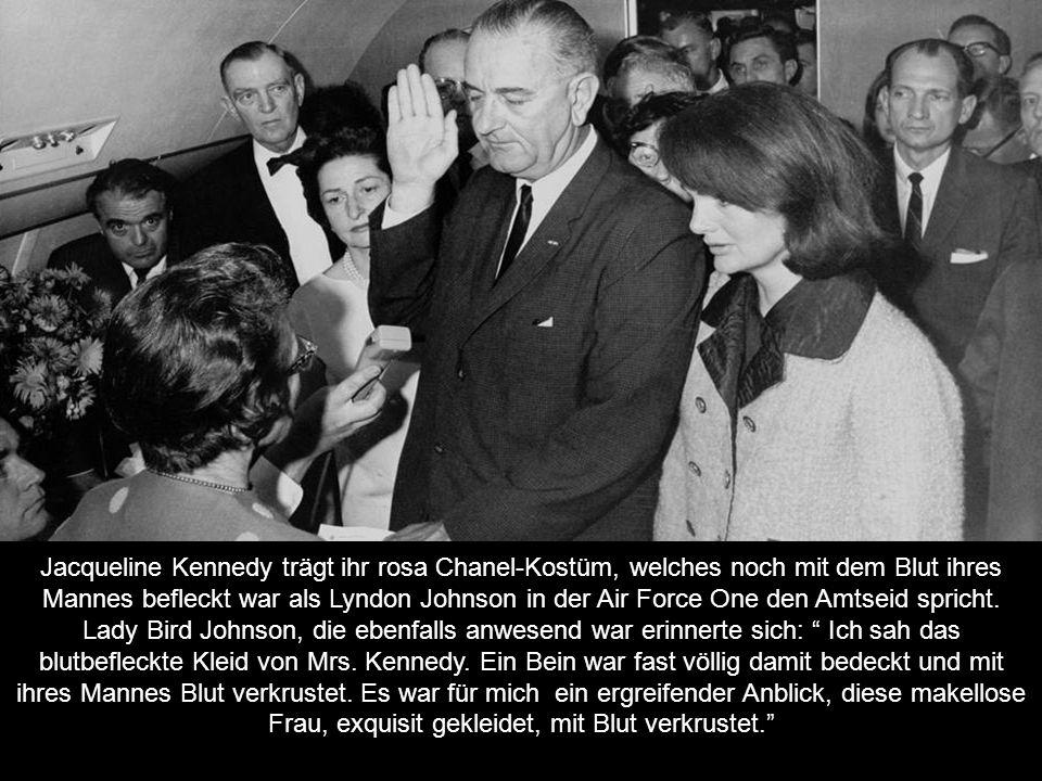 Jacqueline Kennedy trägt ihr rosa Chanel-Kostüm, welches noch mit dem Blut ihres Mannes befleckt war als Lyndon Johnson in der Air Force One den Amtseid spricht.