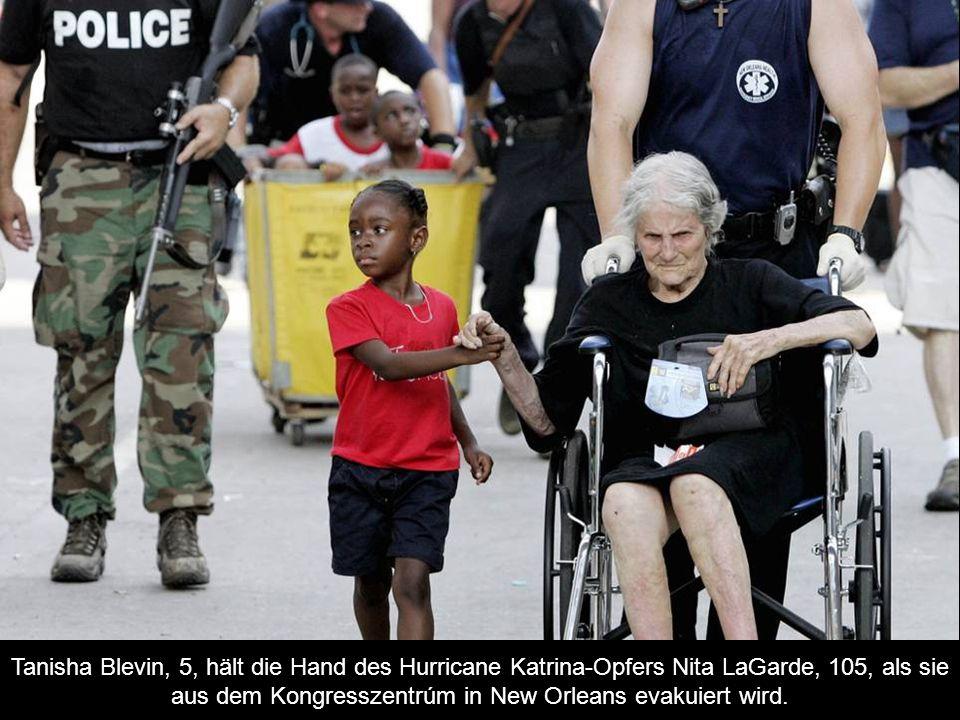 Tanisha Blevin, 5, hält die Hand des Hurricane Katrina-Opfers Nita LaGarde, 105, als sie aus dem Kongresszentrúm in New Orleans evakuiert wird.