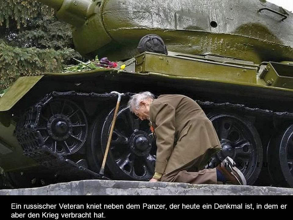 Ein russischer Veteran kniet neben dem Panzer, der heute ein Denkmal ist, in dem er
