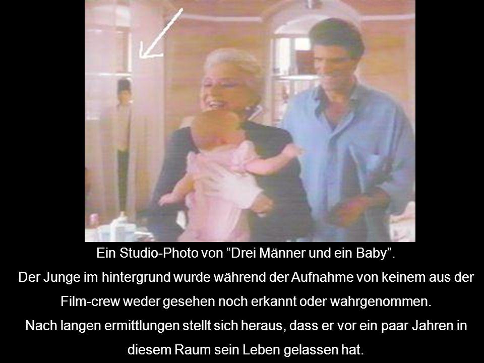 Ein Studio-Photo von Drei Männer und ein Baby .
