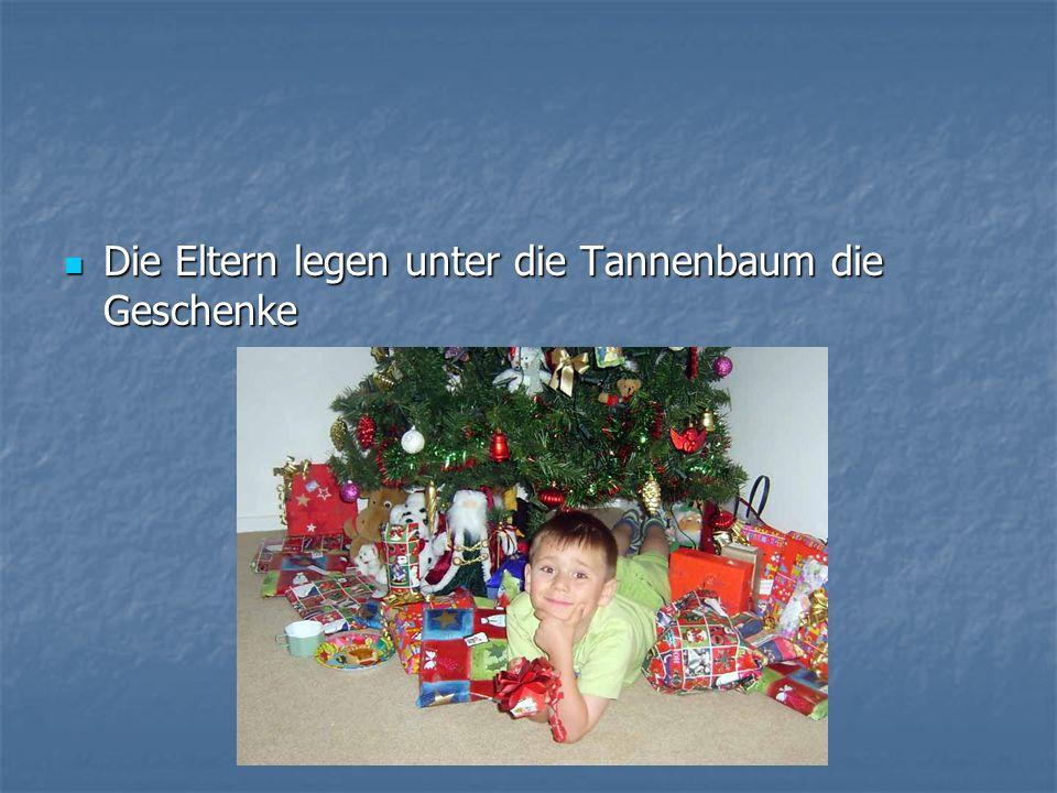 Die Eltern legen unter die Tannenbaum die Geschenke