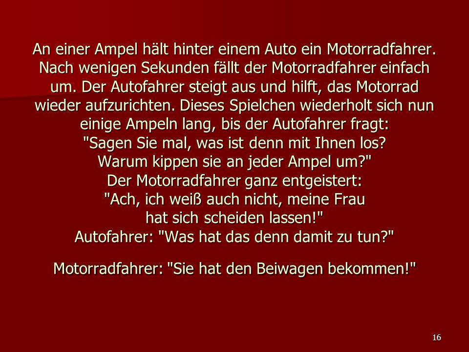 An einer Ampel hält hinter einem Auto ein Motorradfahrer