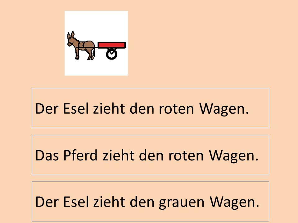 Der Esel zieht den roten Wagen.