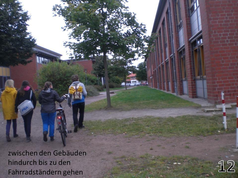 12 zwischen den Gebäuden hindurch bis zu den Fahrradständern gehen