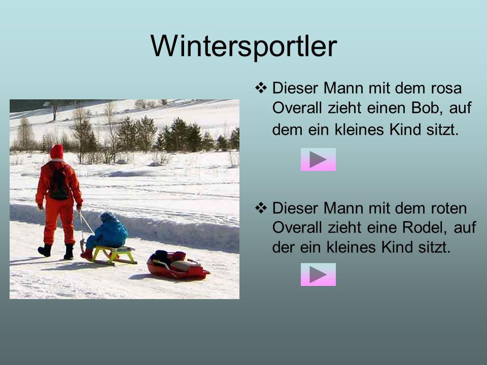 Wintersportler Dieser Mann mit dem rosa Overall zieht einen Bob, auf dem ein kleines Kind sitzt.