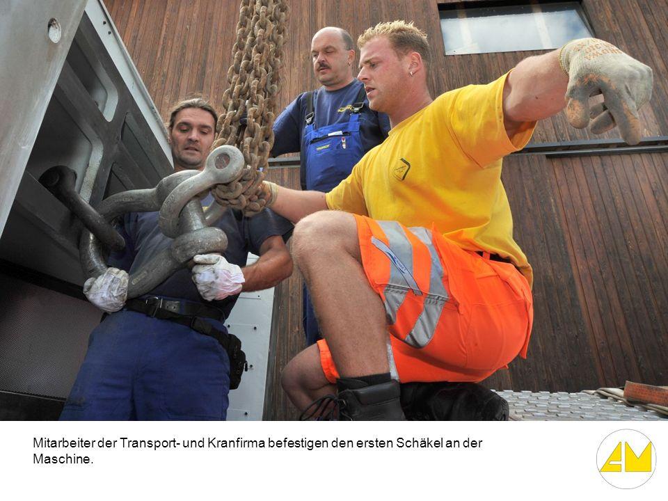 Mitarbeiter der Transport- und Kranfirma befestigen den ersten Schäkel an der Maschine.
