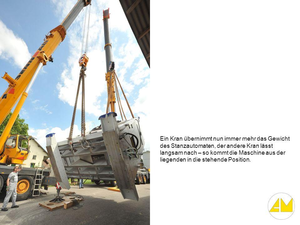 Ein Kran übernimmt nun immer mehr das Gewicht des Stanzautomaten, der andere Kran lässt langsam nach – so kommt die Maschine aus der liegenden in die stehende Position.