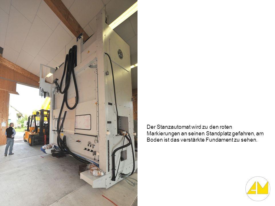 Der Stanzautomat wird zu den roten Markierungen an seinen Standplatz gefahren, am Boden ist das verstärkte Fundament zu sehen.