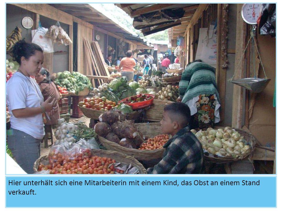 Hier unterhält sich eine Mitarbeiterin mit einem Kind, das Obst an einem Stand verkauft.