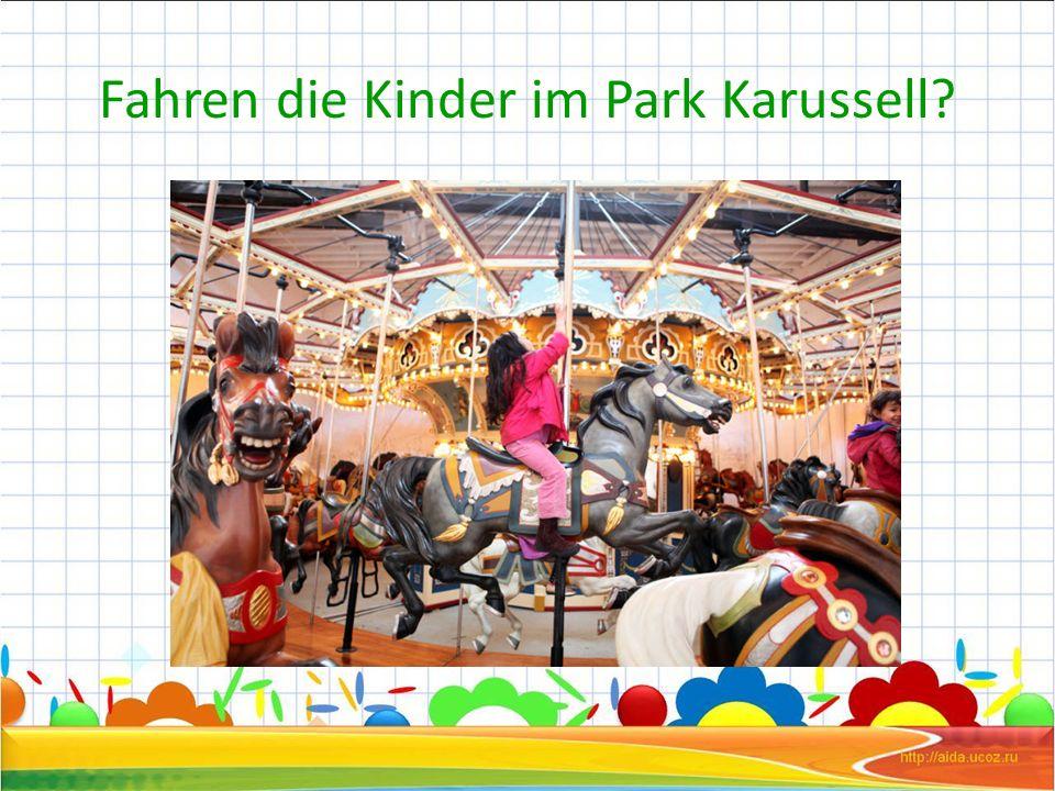 Fahren die Kinder im Park Karussell