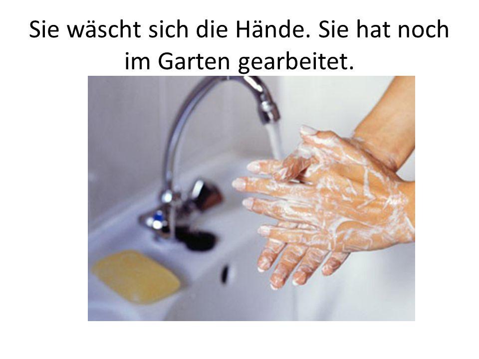 Sie wäscht sich die Hände. Sie hat noch im Garten gearbeitet.
