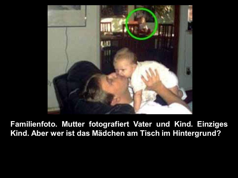 Familienfoto. Mutter fotografiert Vater und Kind. Einziges Kind