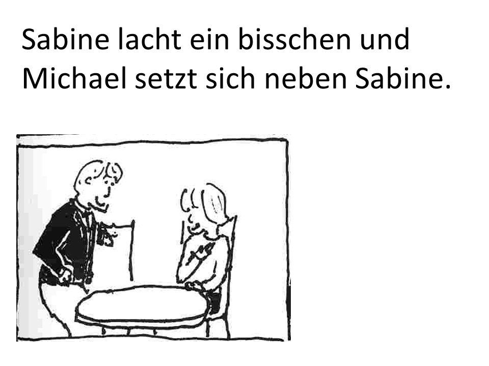 Sabine lacht ein bisschen und Michael setzt sich neben Sabine.
