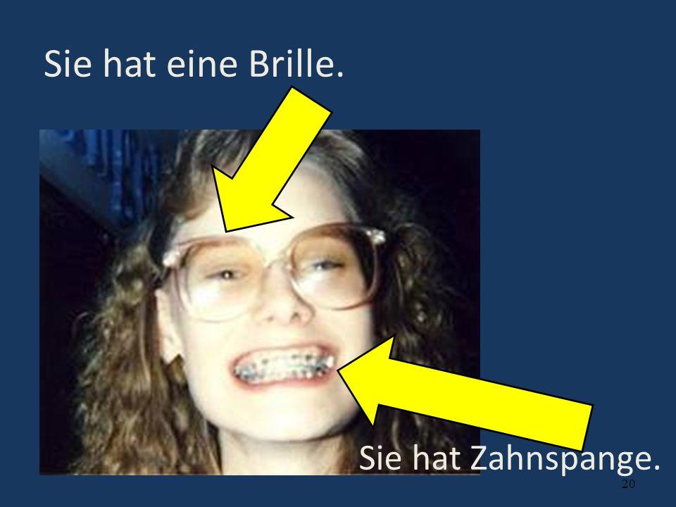 Sie hat eine Brille. Sie hat Zahnspange.