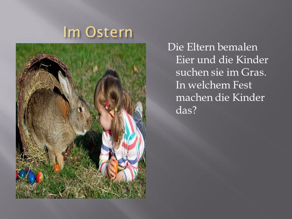 Im Ostern Die Eltern bemalen Eier und die Kinder suchen sie im Gras.